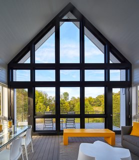 """This large screened porch is a favorite destination of the homeowner. """"She spends a lot of time on the screened porch because it straddles the meadow and the mountains,"""" said Wiedemann. """"And it's directly accessible from the living area and the kitchen."""""""