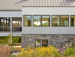 """According to the architects, the screened porch panels (on the left) were site-built by the contractor to have similar dimensions as the Marvin windows (to the right). Dramatic black sashes unite the facade. Thin mull covers between window units blend with the exterior siding, """"which afforded a consistency that we were after,"""" said Wiedemann. Native stone on the foundation is similar to old Virginia farmhouses."""