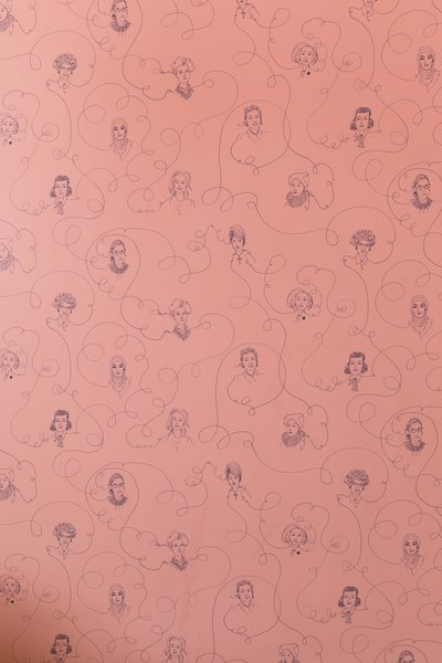 An up-close view at the detail of the wallpaper drawn with portraits of famous female leaders.