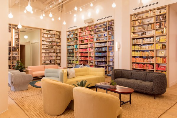 The double-height lending library anchors a corner of the open-plan room. The book collection was curated with Strand Bookstore and includes 2,000 volumes from women authors.