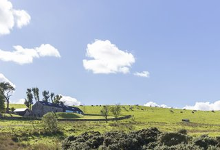 The renovated home is nestled in its country setting with distant views into two valleys.