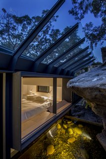 The principal bedroom windows embrace the sandstone rock face. A sloped glass roof shields from rain.
