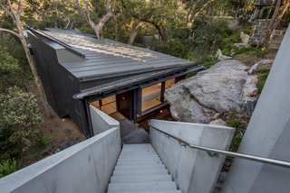 The house sits on a steep site and was positioned below a sandstone crop so as to be concealed from the street. The approach to the house is via a suspended, concrete staircase.