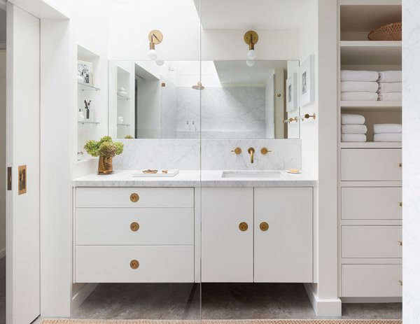The Carrara marble counter and backsplash, concrete floors, frameless mirror, and white cabinets keep the look chic and consistent in the bathroom.