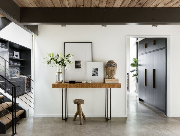 Starting with the front hall, the architects have opened up the enclosed stairwell and utilized a lighter palette to bounce natural light around. White walls, concrete floors, and minimal trim produce a streamlined backdrop.