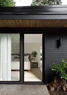 Generous overhangs and period lighting speak to the home's original era, while sliding glass doors add a modern touch and create easy outdoor access.