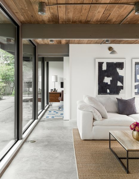 """In the family room, """"short ribbon windows were replaced with a wall of glass"""" for a effortless indoor/outdoor flow."""
