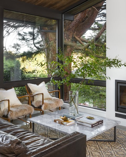 """While the window openings in this cozy corner are the same as before, the architects tweaked the frames. """"The layout of the windows was flipped so that the horizontal division was rail height, rather than obstructing sight-lines when standing,"""" the team explains."""