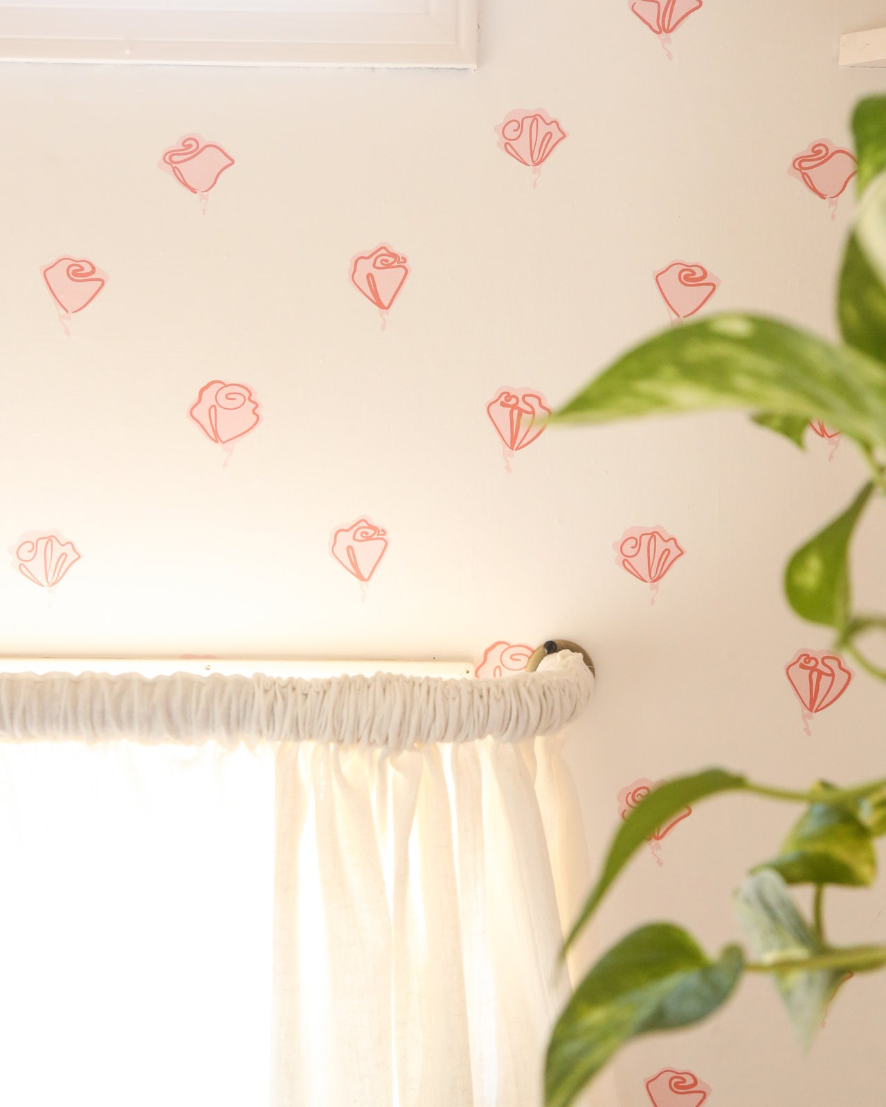An accent wall at the head of the bed sports Hygge and West wallpaper in a rose pattern, in homage to the newly refreshed camper's name.