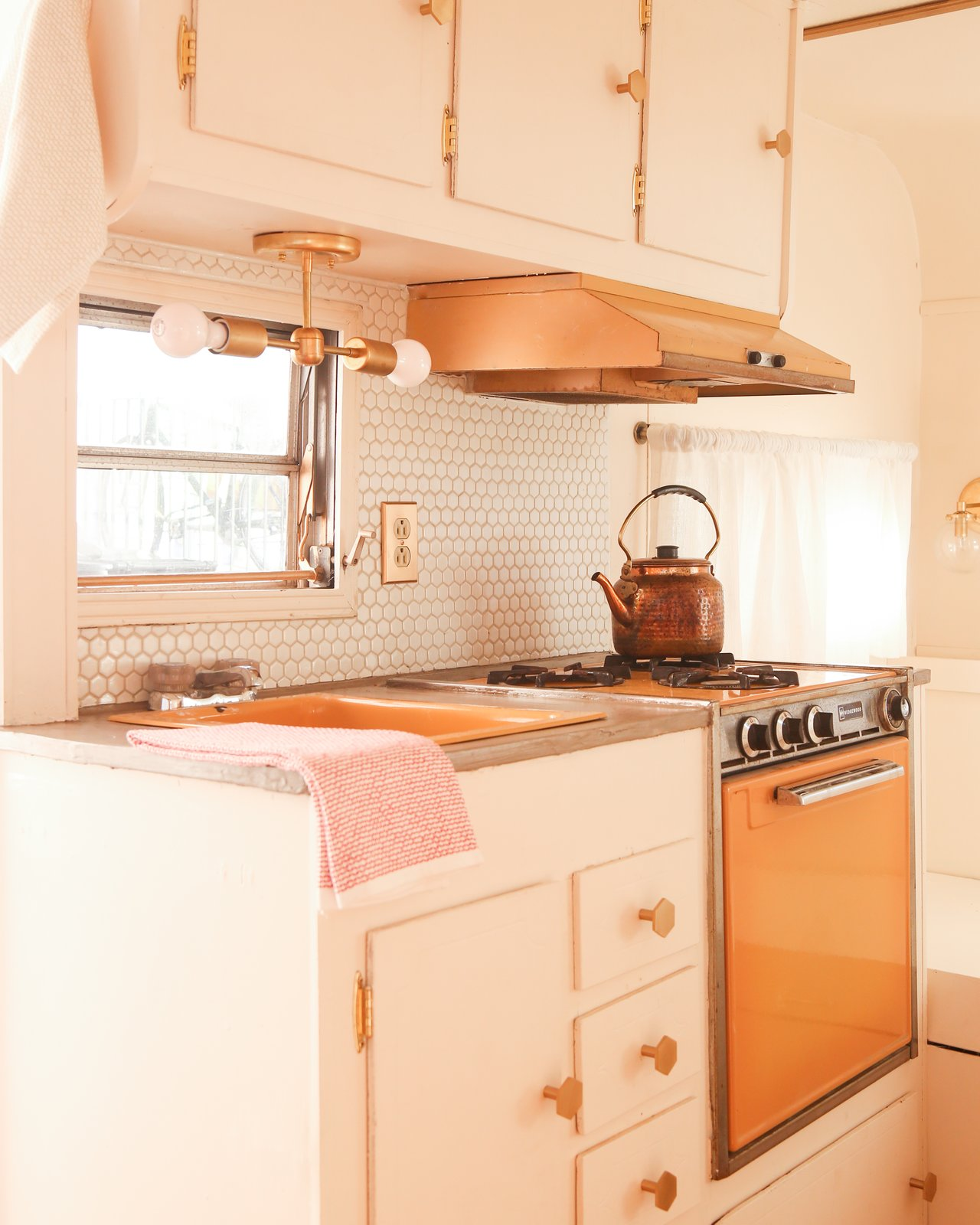 In the petite kitchenette, the original orange-tinted enamel of the sink and stove was spruced up with concrete overlay on the counters, a hex tile backsplash, and new brass accents. The original cabinets were refreshed with the same paint color as the interior walls, then adorned with brass hinges and hex-shaped pulls.