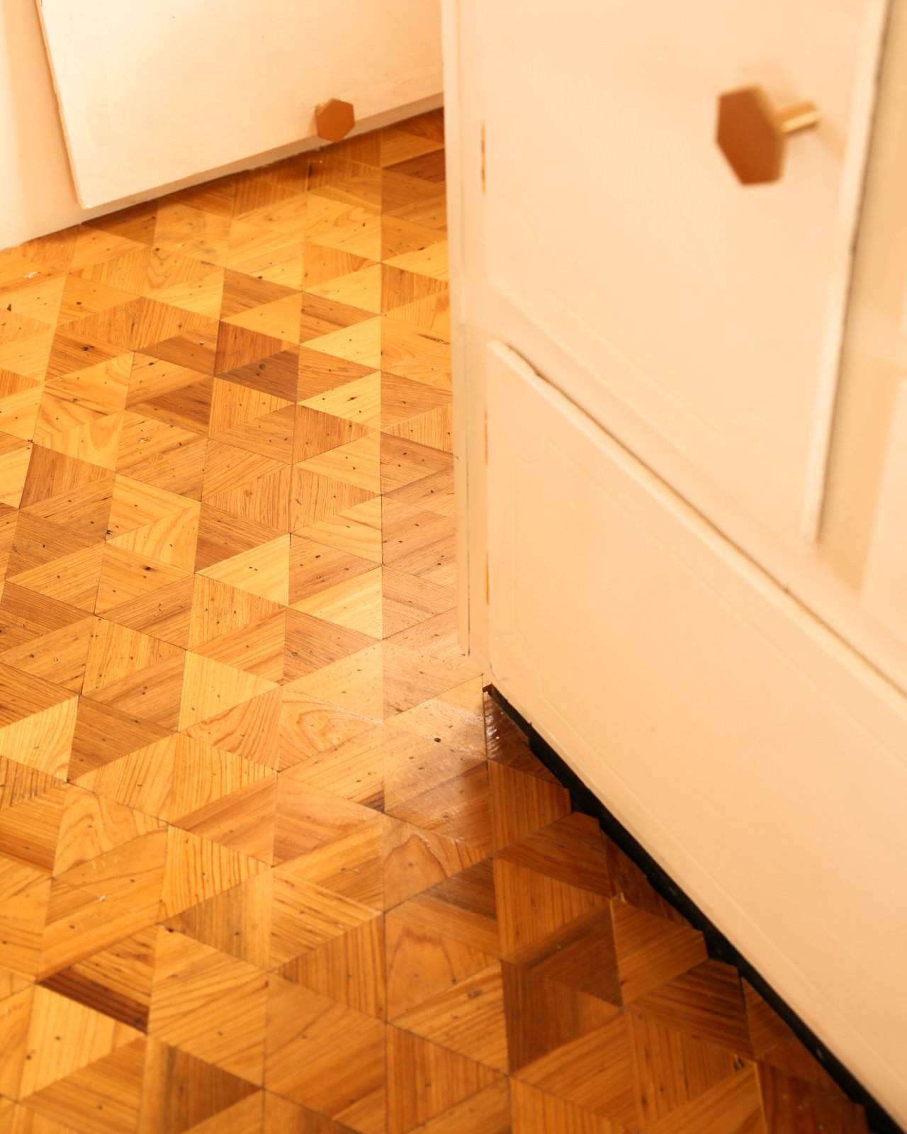 For the jaw-dropping, 40-square-foot floor makeover, peel-and-stick tile was traded for a mosaic of 3-inch wood triangles cut from reclaimed Cypress.