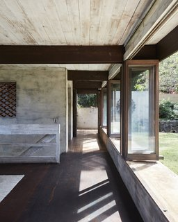 Folding doors line the courtyard. Cinder block walls are coated in stucco made with sand from the community of Waimānalo, and mixed with concrete and water.