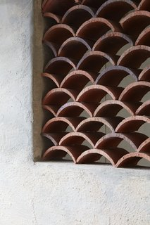 The architect created multiple decorative wall cut-outs throughout the home to facilitate ventilation, composed of roof tiles laid in a wave pattern.