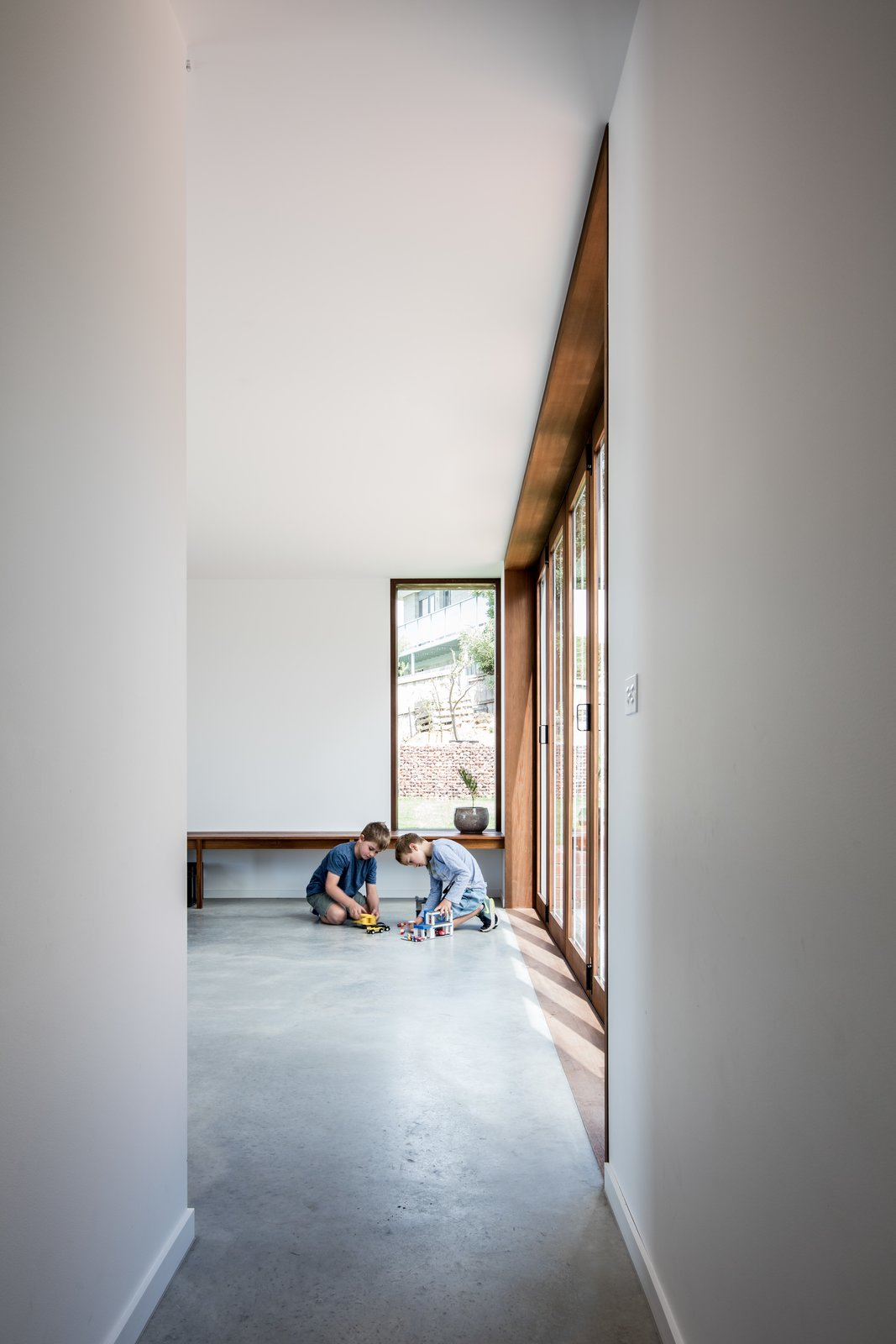 """In the new sitting room, the architects opted for timber-framed windows and doors. """"In this space the fixed joinery elements invert the original material strategy of the house,"""" they write."""