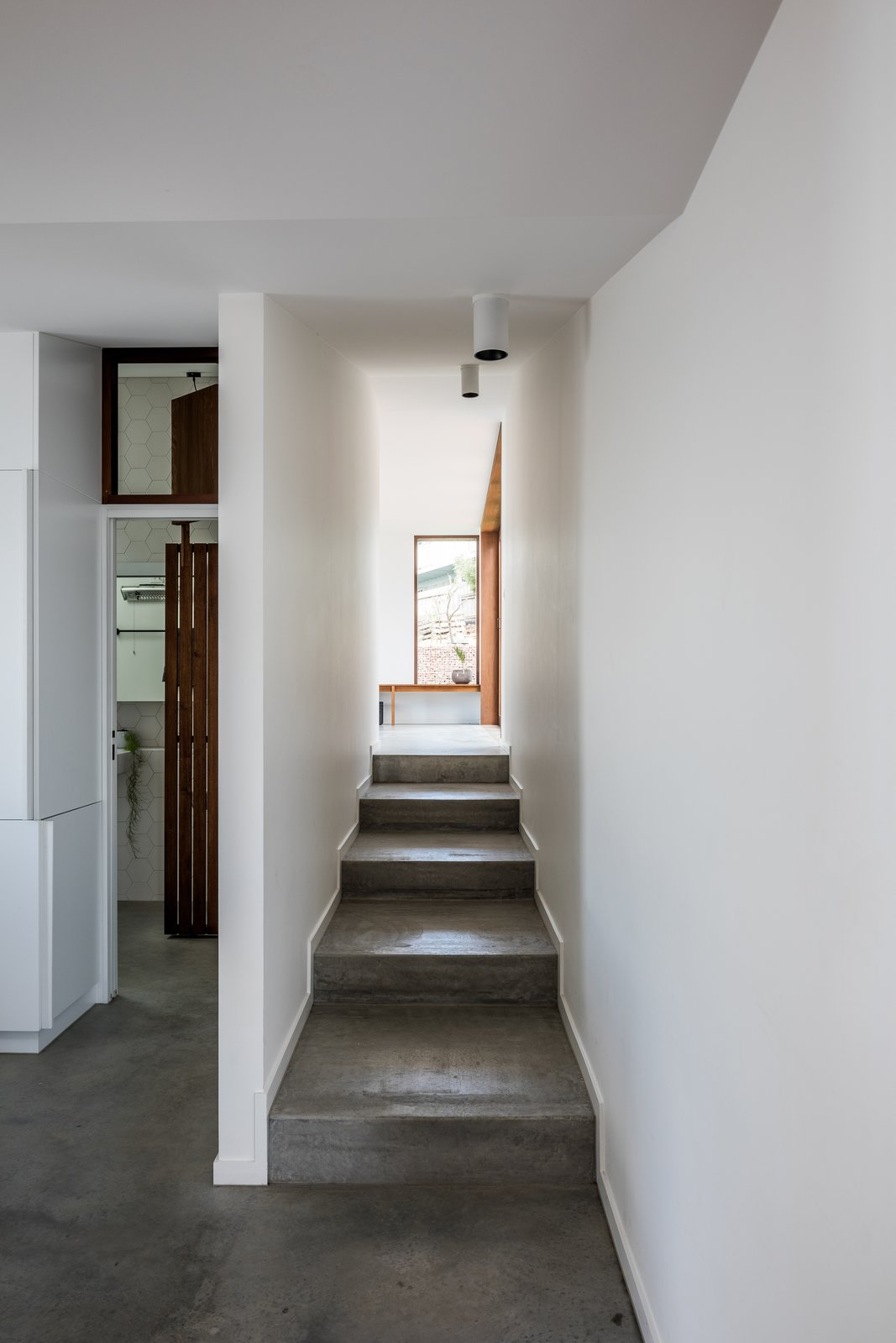 The architects signified the extension with a waxed concrete floor. To the left of the staircase is a new bathroom and laundry. The stairs lead up to a new sitting room that connects to the new brick garden terrace.
