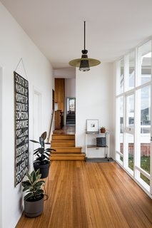 Inside the entry, which affords a view through the house towards the extension, Emery's original palette combines white walls with wood floors.
