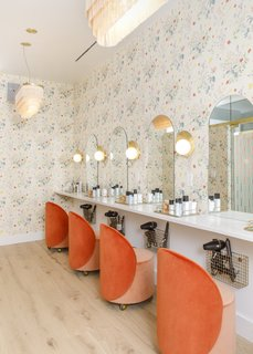 In the beauty room, floral wallpaper from Caitlin McGauley picks up the tangerine color of the chairs from Douglas & Bec. Wall light sculptures from Cedar & Moss illuminate the mirrors.
