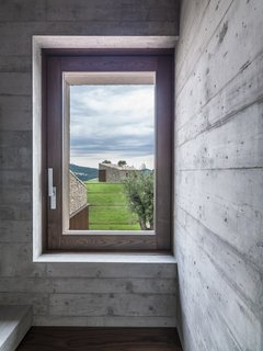 A walnut window frame captures the view outside.