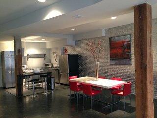 "Flashy silver brick, bright red accents, and a black utilitarian floor obscure the loft's better qualities: high ceilings and exposed wood beams. Coffey notes there was also ""an open enclave between the kitchen and living area [that] had a raised platform and no real programmatic use."""