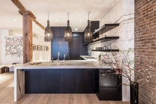 By removing the raised platform that originally had no use, the team was able to double the size of the kitchen and add in a new bathroom on the main floor. The pendants over the peninsula were sourced by the homeowner from AY Lighting, and now echo the dark tones of the white oak cabinetry, which sport walnut interiors.