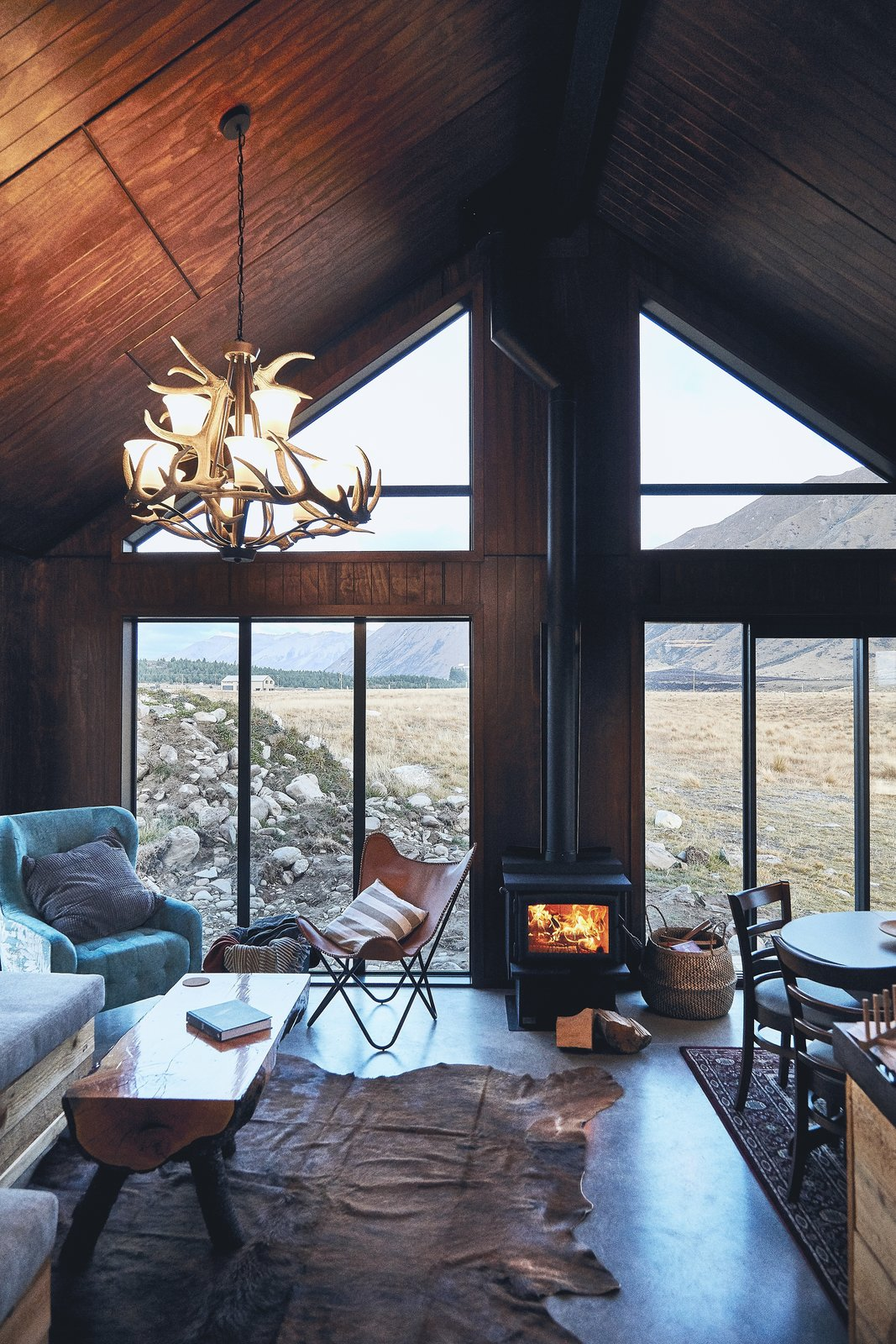 """Living Room, Chair, Sofa, Concrete Floor, Coffee Tables, Wood Burning Fireplace, Pendant Lighting, and Rug Floor """"With this cabin I wanted something that was robust, so you could enter after an outdoor activity, kick your boots off, start the fire and put some food on,"""" says Kenny. """"But at the same time have a feeling of space with the high ceilings, and some luxury and comforts of modern living like a nice shower and great water pressure.""""  Photo 2 of 9 in You Won't Want to Leave This Cozy Cabin in New Zealand"""
