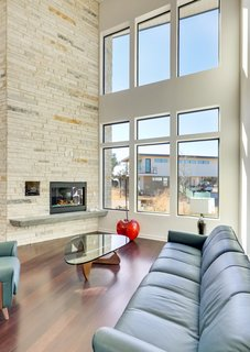 The double-height living room features a dramatic fireplace column, wood floors, and generous windows.