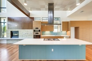 The kitchen features an expansive, quartz-topped island and Bosch appliances.