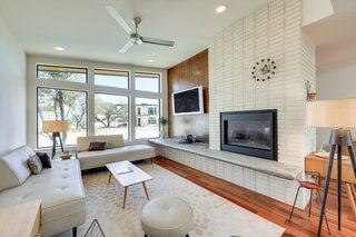 The open-concept living room features a fireplace clad in white brick.