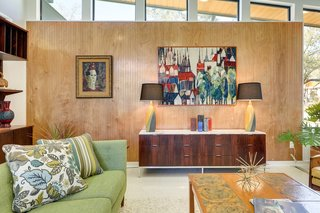 A wood-paneled feature wall is topped with trapezoid-shaped, clerestory windows.