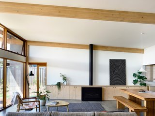 In the living room, the horizontal lines of the timber beams at the ceiling echo the bespoke cabinetry that surrounds the gas fireplace. The dining room pendant is the Gubi Semi Pendant.