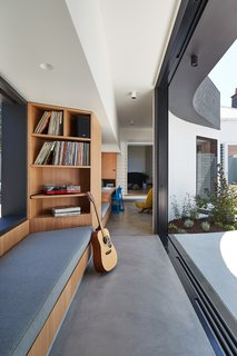 The connecting corridor, or circulation spine, uses built-ins to create space for various activities, such as a family study, a music spot, and reading nooks.
