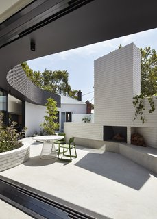 In this view, one can see how the curved addition makes space for an outdoor seating area with a fire pit, and eventually meets the clapboard form of the original house.