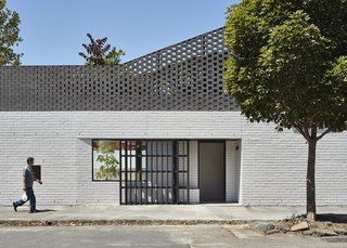 """A view of the new eastern-facing front door. """"At the second level, brickwork gradually opens up to become a perforated brick screen for the roof top deck,"""" explain the architects."""