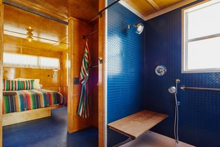 Inside this trailer, the blue shower and floor contrast warmly with the birch interior.