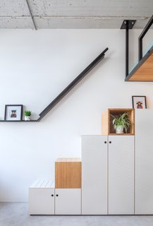 The staircase leading to the bed also functions as a large wardrobe.