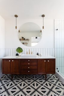 In a bathroom, a credenza found on Etsy was topped with marble and converted to a vanity. Tulum tile from the Cement Tile Shop covers the floors while elongated subway tile, laid in a vertical grid, updates the walls. Schoolhouse Electric pendants complete the look.