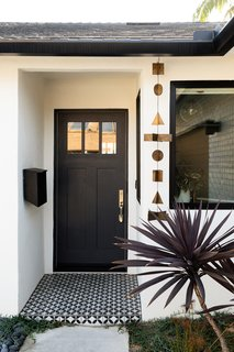 At the entry, Naber improved the welcome via a new door with a fresh coat of black paint and brass hardware. A Clé tile threshold and a hanging mobile from Anthropologie further spruce the spot.