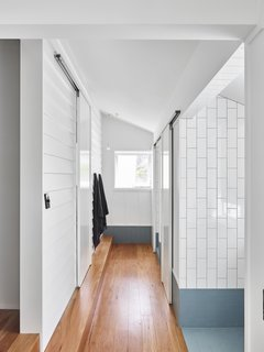 A new bathroom wing upstairs hosts private toilet and shower rooms, as well as separate spots for bathing and accessing the sink. It further pushes the theme of thoughtful material connections, using tile instead of concrete to contrast with the wood.