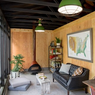 Carstensen purchased the vintage Malm fireplace in Los Angeles on a work trip and had it shipped to Portland. He's hoping to install it in time for the fall season. The interior of the porch is outfitted with a mix of furnishings, both vintage and new. The rug, shelf unit, and loveseat are all from the locally based Schoolhouse Electric, as are the ceiling lights: Factory Light No. 7 in Green.