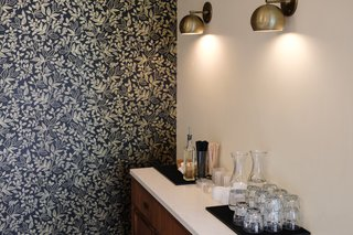 The dark-hued wallpaper from Rifle Paper offsets the brass sconces from Schoolhouse Electric.