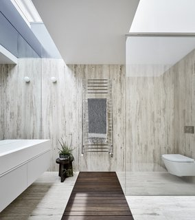 In the bathroom, skylights have been placed in the existing roofline to bring in more natural light. A glass partition and frameless mirror visually expand the space.