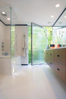 In the master bathroom, a large pivot door creates gracious indoor/outdoor flow.