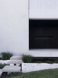 """Blackened, recycled wood slats define the front entry alcove. """"The design of House A was originally intended to challenge the status quo of oversized and low-quality housing in Western Australia,"""" say the architects."""