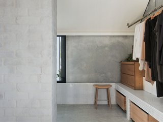"""According to the architects, the firm """"merged spaces and volumes to achieve simultaneous privacy and openness without the need for doors and walls."""" An open closet adjoins the upper level ensuite bathroom and looks neat and tidy with detailed finishes that are consistent with the rest of the house."""