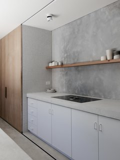 """In the kitchen, white concrete counters top white cabinetry and abut a tile accent wall. The streamlined palette of the house """"originated from a desire to have a space to unwind in that wasn't over-saturated with trends or design features or glossy plastic finishes,"""" say the architects."""