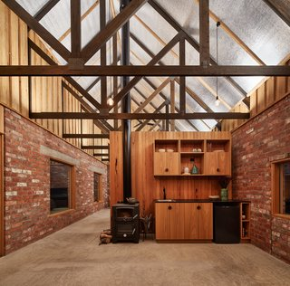 "Salvaged brick was left unfinished on the interior, without a ""sheet of plasterboard in sight,"" the architects continue to explain. Reflective roof insulation at the ceiling redistributes the light from concealed LED fixtures at the timber trusses."