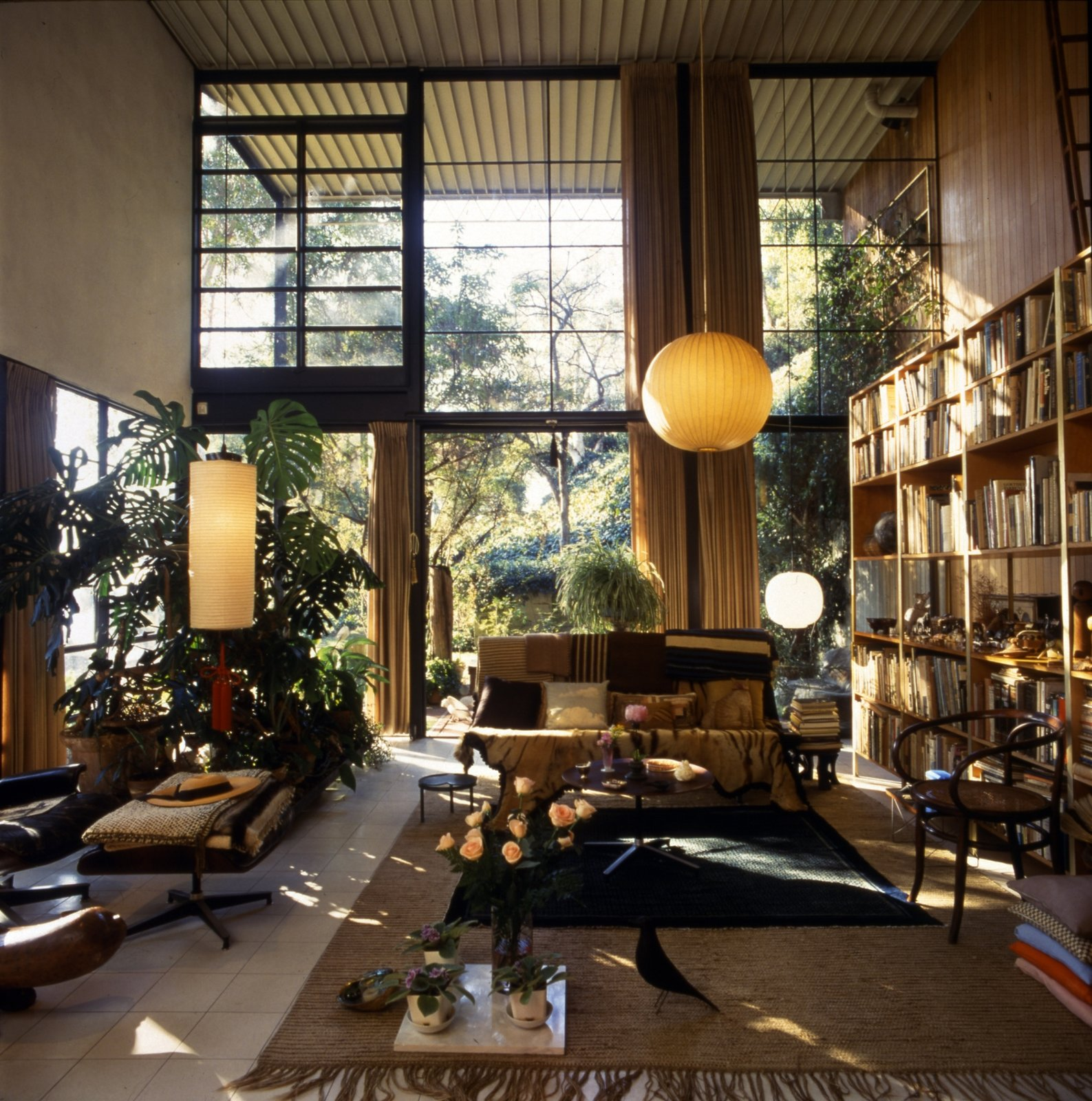 Living Room, Floor Lighting, Pendant Lighting, Coffee Tables, Chair, Sofa, Rug Floor, End Tables, Ceramic Tile Floor, and Bookcase In 1949, the Eameses designed and built their home in Pacific Palisades, California, as part of the Case Study House Program, and it has since become an icon of post-war residential design.  Photo 3 of 8 in Catch 'The World of Charles and Ray Eames' at the End of its Tour in Oakland