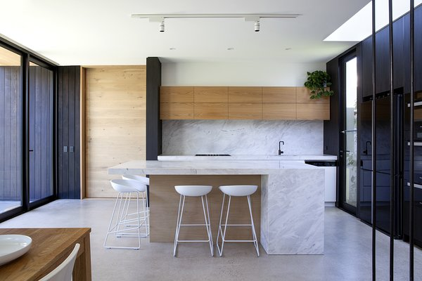 Oak and concrete meet a substantial marble countertop and backsplash in the kitchen.