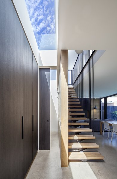"""A staircase with floating oak stair treads and a continuous steel railing goes up to the second floor. The cupboards on the left are fronted with the same """"Ravenswood"""" panels, and a skylight floods the space with light."""