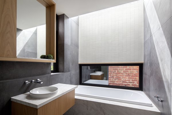 In a bathroom, charcoal walls echo the darker finish of the prefabricated panels elsewhere, and a skylight makes the small space feel bigger.